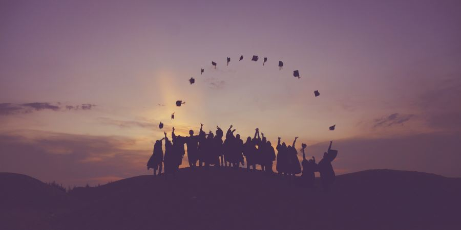 Group of graduated students tossing caps