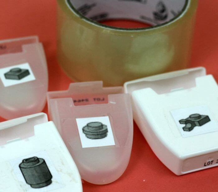 Tape the Lego labels onto the containers with clear tape