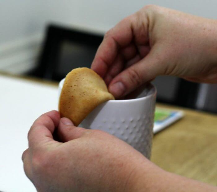 Use the edge of a cup to fold over the fortune cookie.