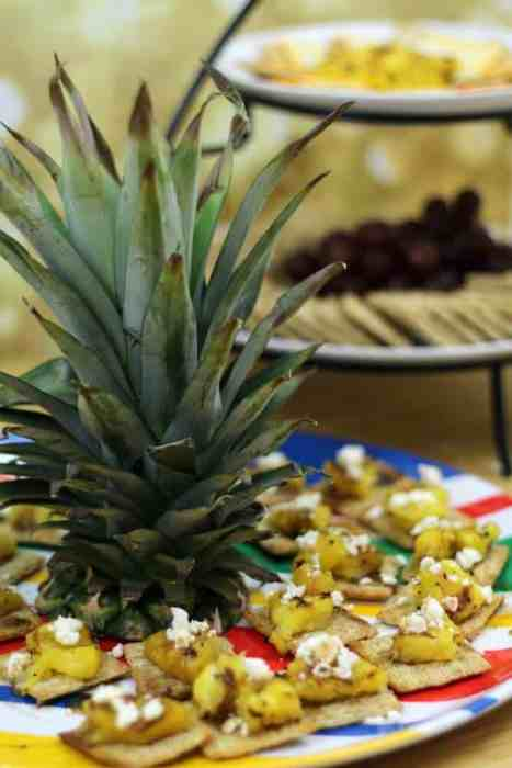 Crackers topped with grilled pineapple, feta, and balsamic viniagrette make sweet and savory summeretime snacks