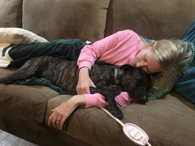beautiful woman snuggling with dog