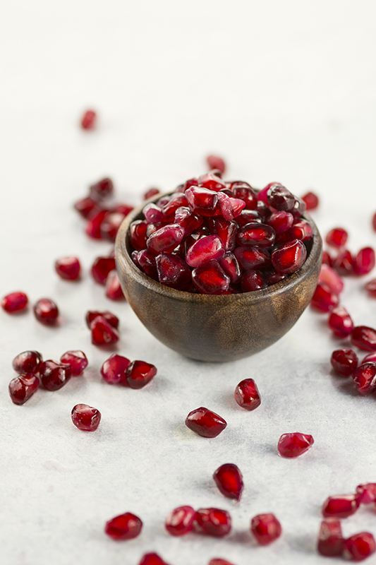 Pomegranate and Walnut Guacamole l pomegranate seed arils on white
