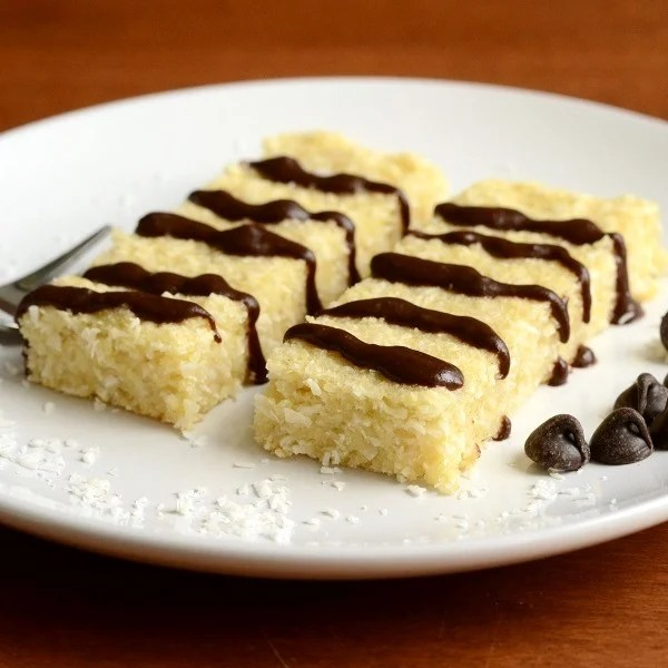 These coconut bars with chocolate drizzle are a delicious treat. Coconut has so many health benefits, and you can't go wrong with chocolate on top. Delicious healthy dessert recipe!