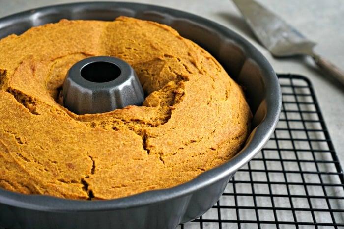 Pumpkin gingerbread bundt cake cooling on rack