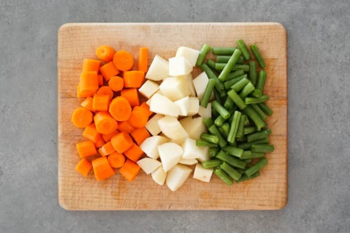 Carrots, potatoes, and green beans on a cutting board