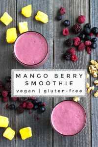 Mango berry smoothie on a board with fruit and walnuts