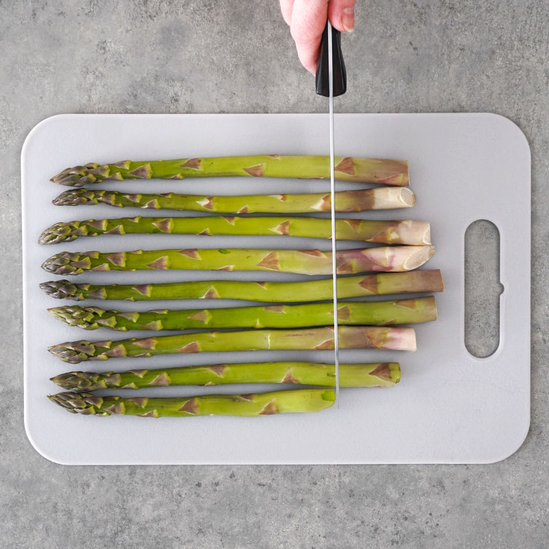 Cutting the stems off the asparagus on a cutting board