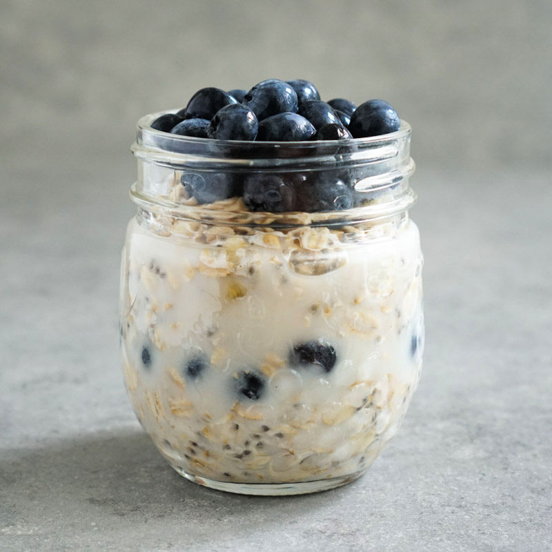 Stacking blueberry overnight oats ingredients in a jar - top layer