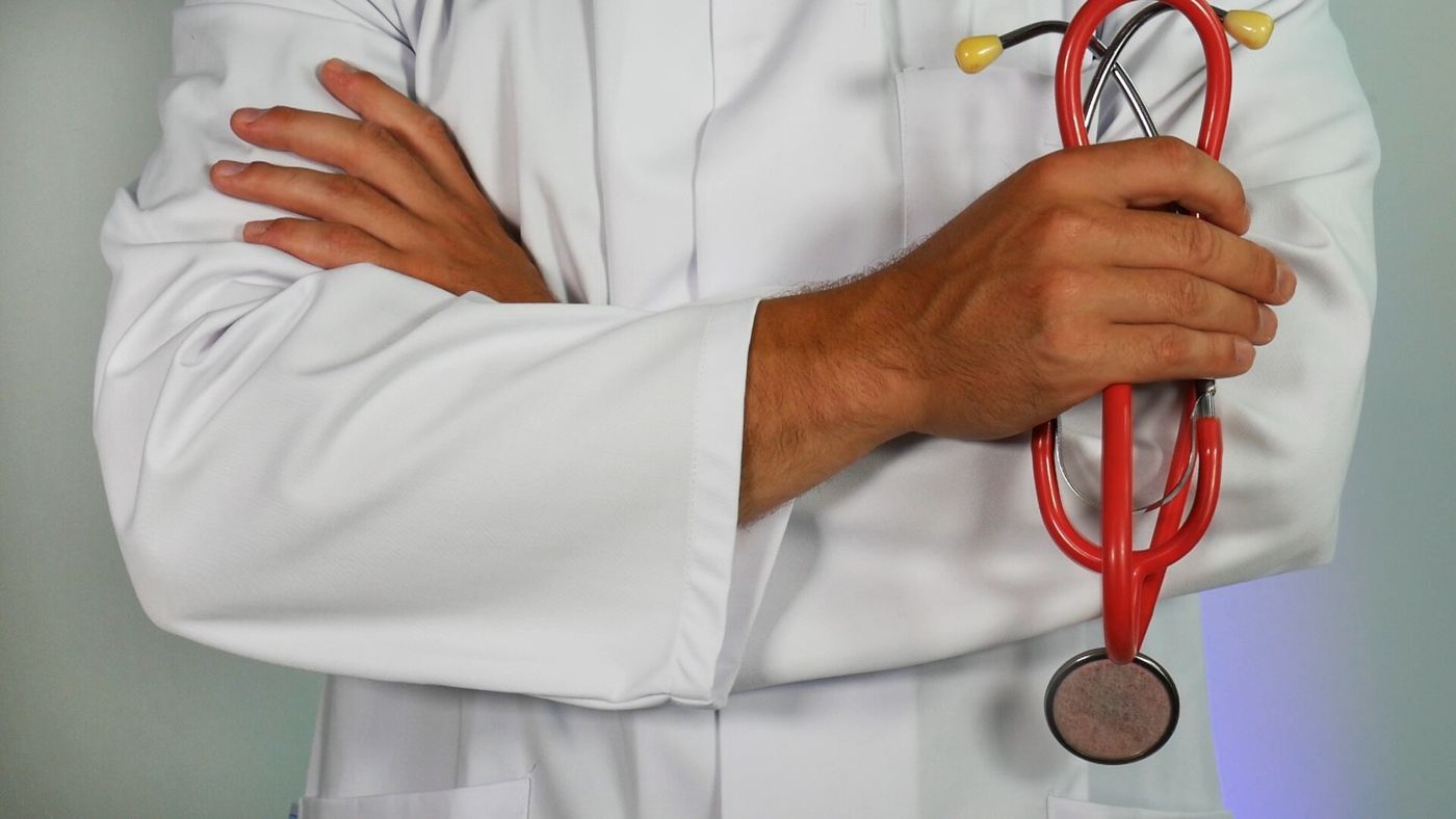doctor in white lab coat with crossed arms while holding red stethoscope