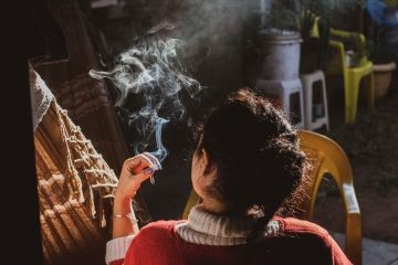 light-skinned person with dark hair in a bun smoking a cannabis cigarette
