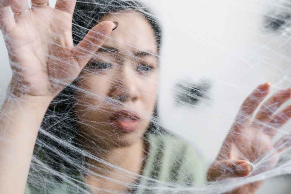 close up photo of a fearful woman trapped in a spider web
