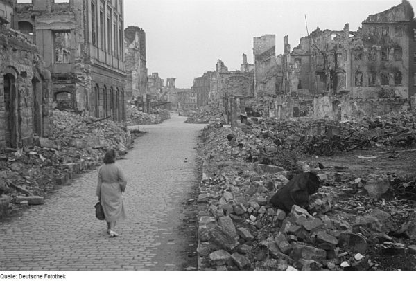 Woman walks through bombed-out city street in Dresden, Germany; World War Two