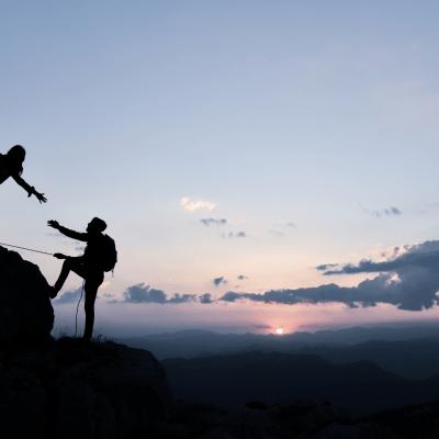 Women and Man rock climbing at sunset