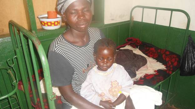 Nyamatora, recovering from severe malaria, sits on her mother's lap in the Panyadoli Health Center.