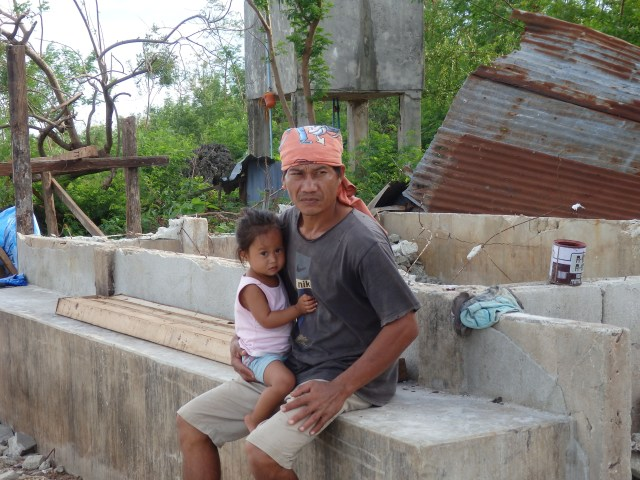 A Father and His Daughter in front of Their Destroyed House