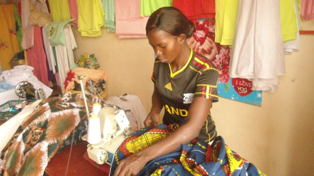 Auma Santa over-locking her customer's kitenge skirt