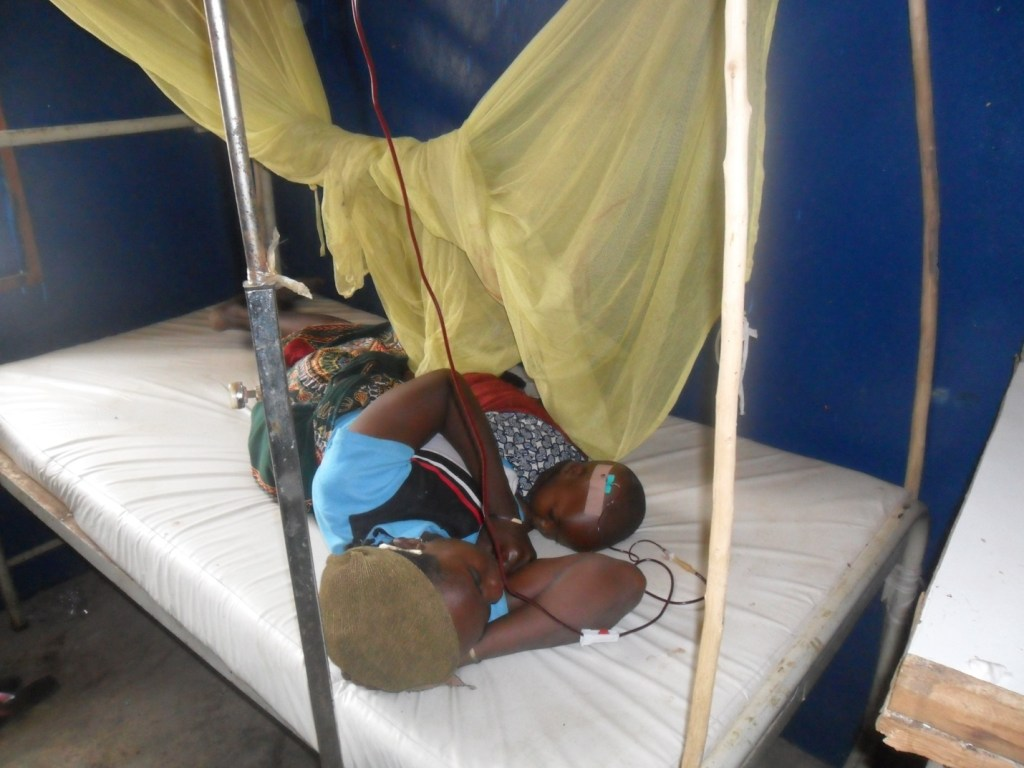 Rasheed and his mother lay in bed in the clinic