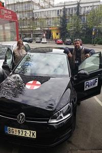 team posing by new car