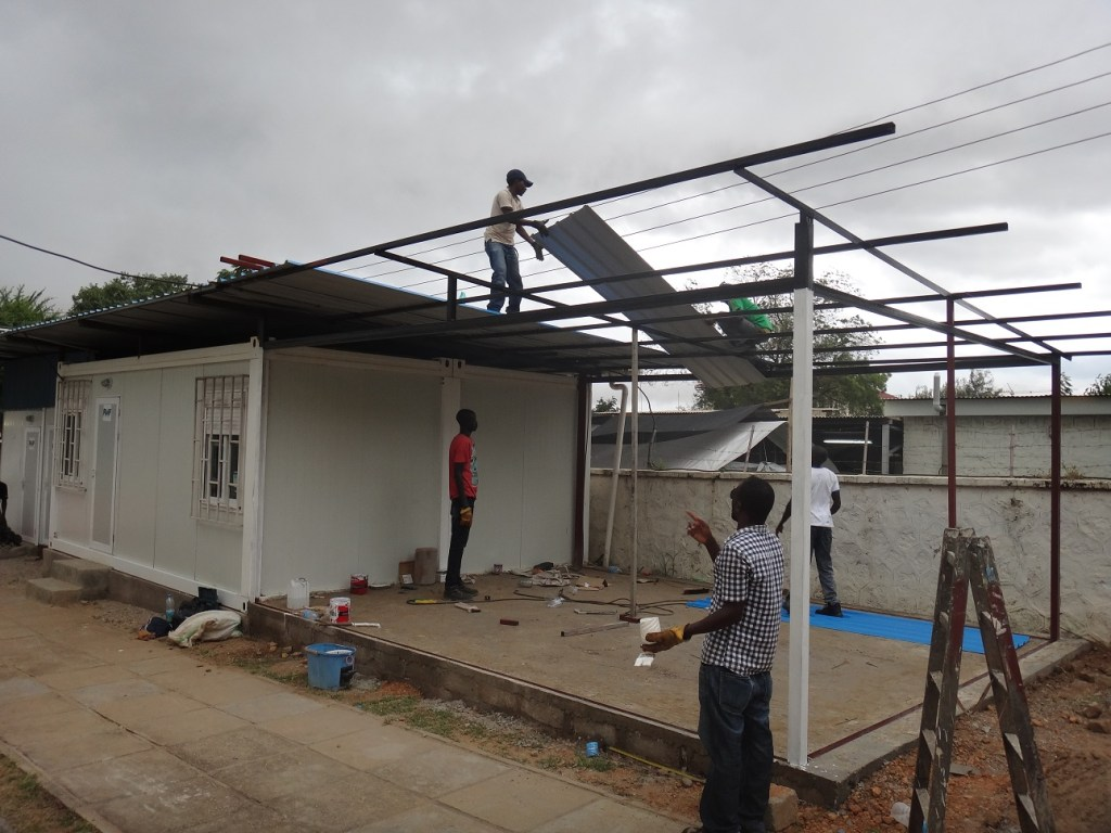 Technicians attaching the roofing of the new office space annexed to the existing structure