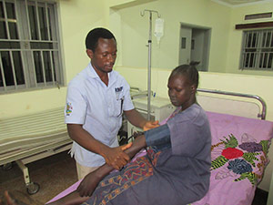 Dr. Robert treating an expectant mother in the Maternity ward expansion, newly constructed by RMF