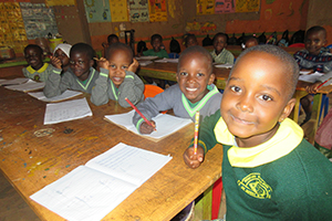 Children smile at the camera while sitting at tables with paper and pencils.