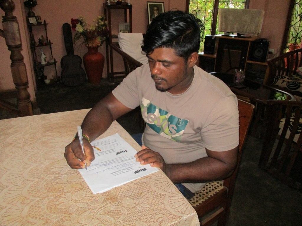 Tharindu signs a document