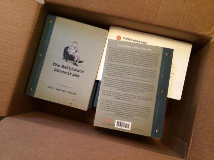 Copies of The Baltimore Atrocities by John Dermot Woods in an open box from the publisher