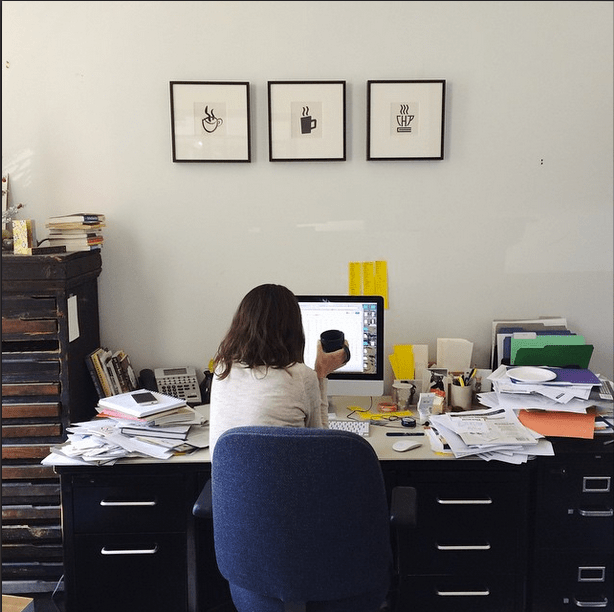 A classic view of Caroline working on spreadsheets (and her messy desk). --@coffeehousepress