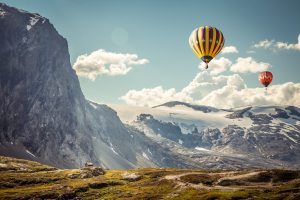 air ballons flying by mountains