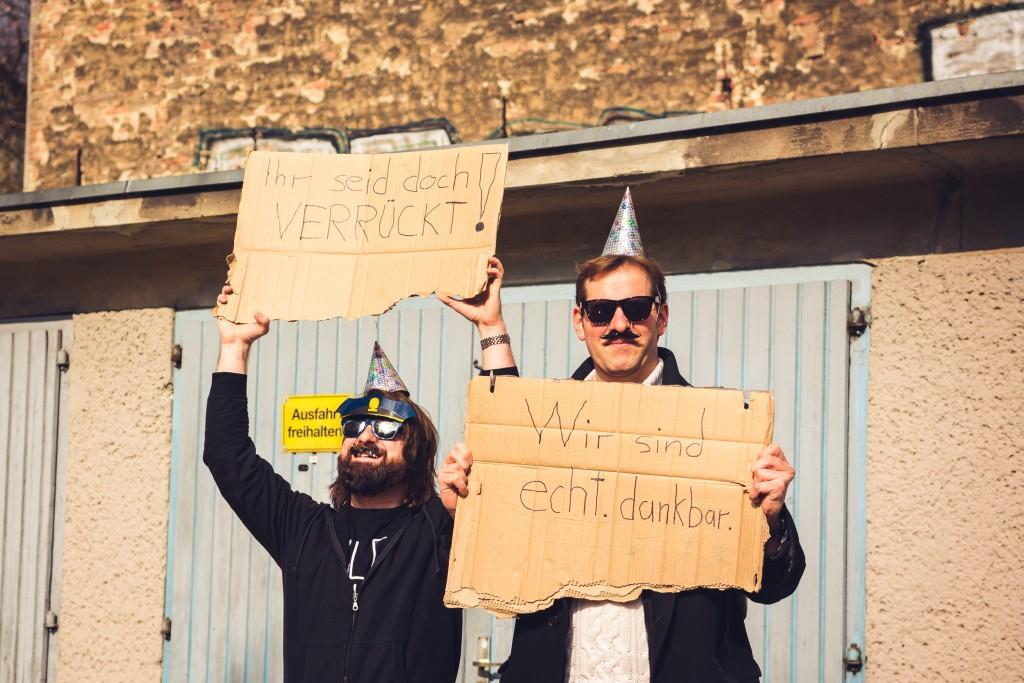 Andi und Jochen stehehen mit witzigen Bildern vor einer Garage
