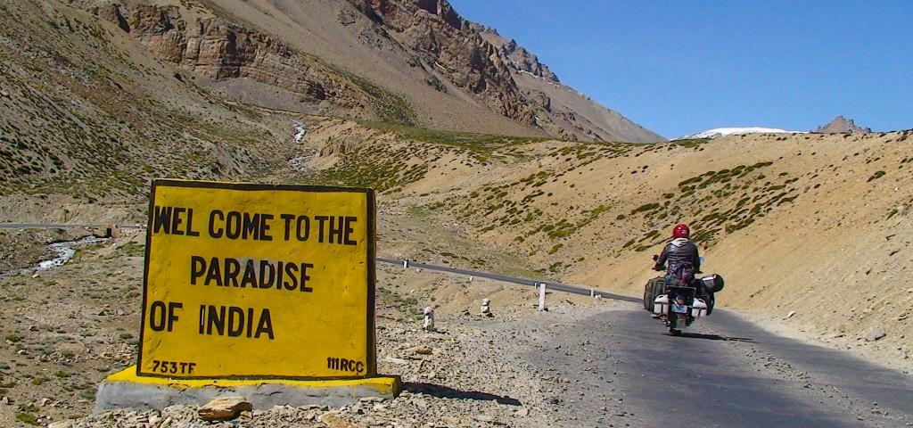 """Straßenschild im Himalaya mit Aufschrift """"Welcome to the Paradise of India"""", daneben ein Motorrad"""