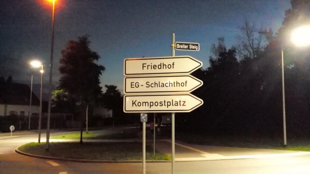"""Drei Verkehrsschilder untereinander: Auf dem oberen steht """"Friedhof"""", auf dem mittleren """"EG-Schlachthof"""" und auf dem unteren """"Kompostplatz"""""""