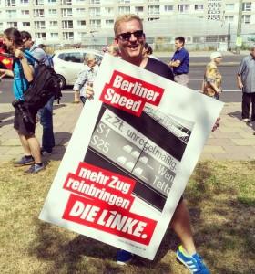 """Alex Jahns, Die Linke Berlin, hält Plakat hoch mit der Aufschrift """"Berliner Speed - mehr Zug reinbringen. Die Linke."""""""