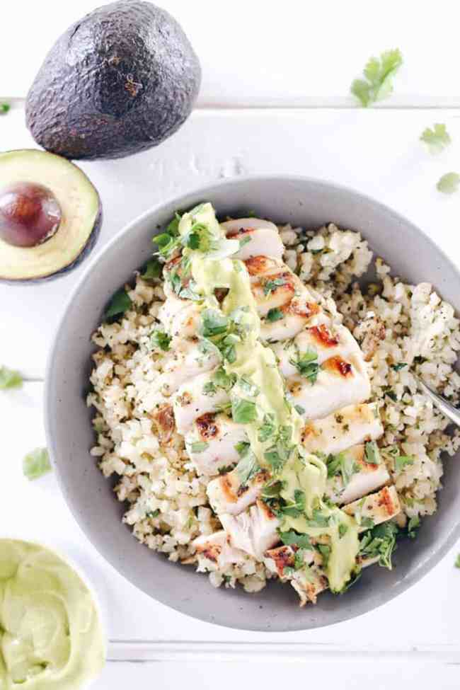 This cilantro lime chicken bowl is everything you need for a EASY Paleo + Whole 30 meal. Marinated chicken over cauliflower rice with a creamy avocado sauce! Paleo, Whole30, Gluten-Free and Dairy-Free. | realsimplegood.com