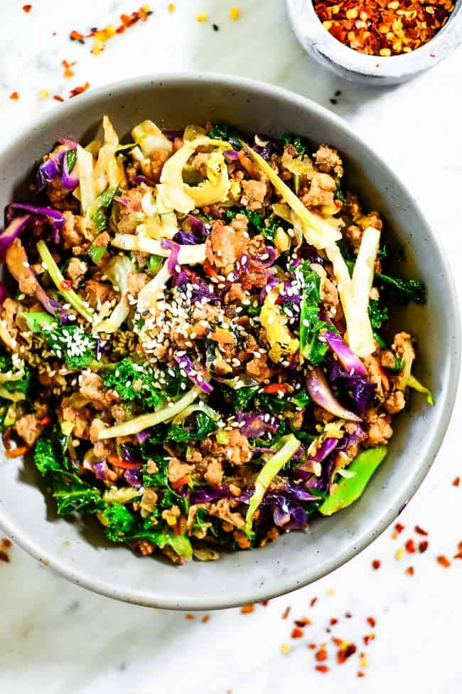 Egg roll in a bowl with sesame seeds on top. Made with cruciferous veggies, ground pork and a savory sauce.