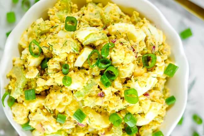 Healthy egg salad in a bowl with chopped green onion garnish.