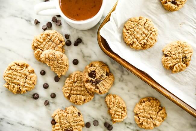 Low carb cookies spread out on marble and cookie sheet with chocolate chips sprinkled about.