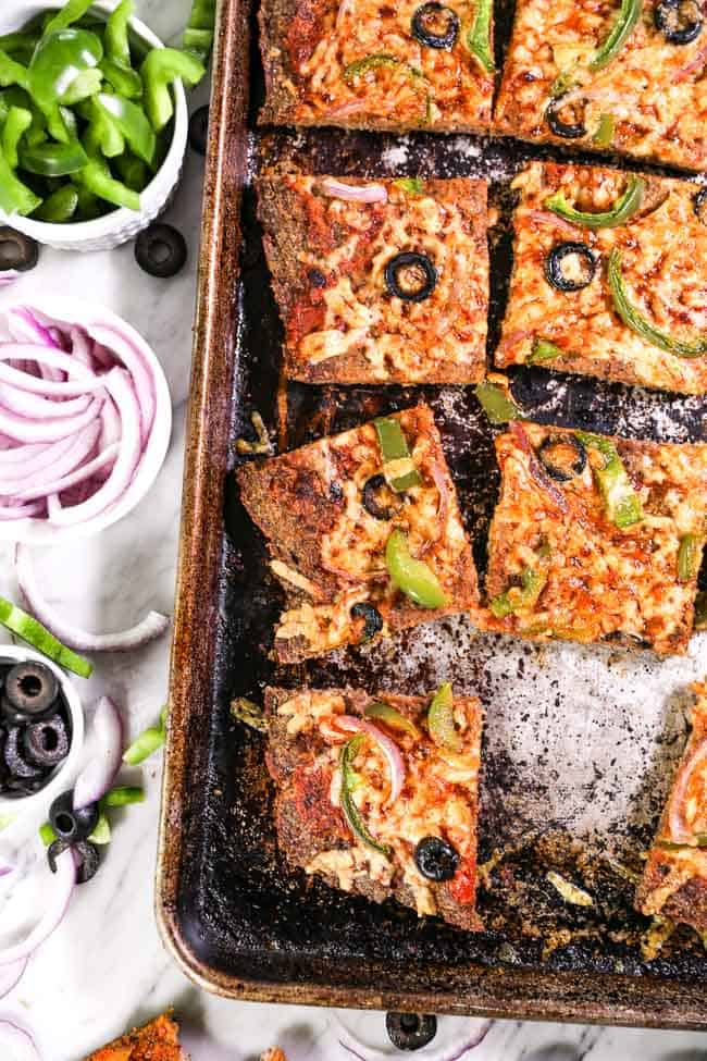 Cut up Meatza in sheet pan with toppings on side and piece missing vertical image