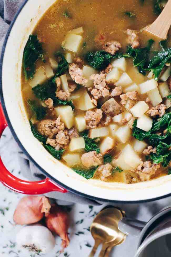 Curling up with a big bowl of this Paleo sausage soup feels so comforting and soul-satisfying. It's filled with roasted garlic, potatoes and kale. Paleo, Whole30 and Dairy-Free. | realsimplegood.com