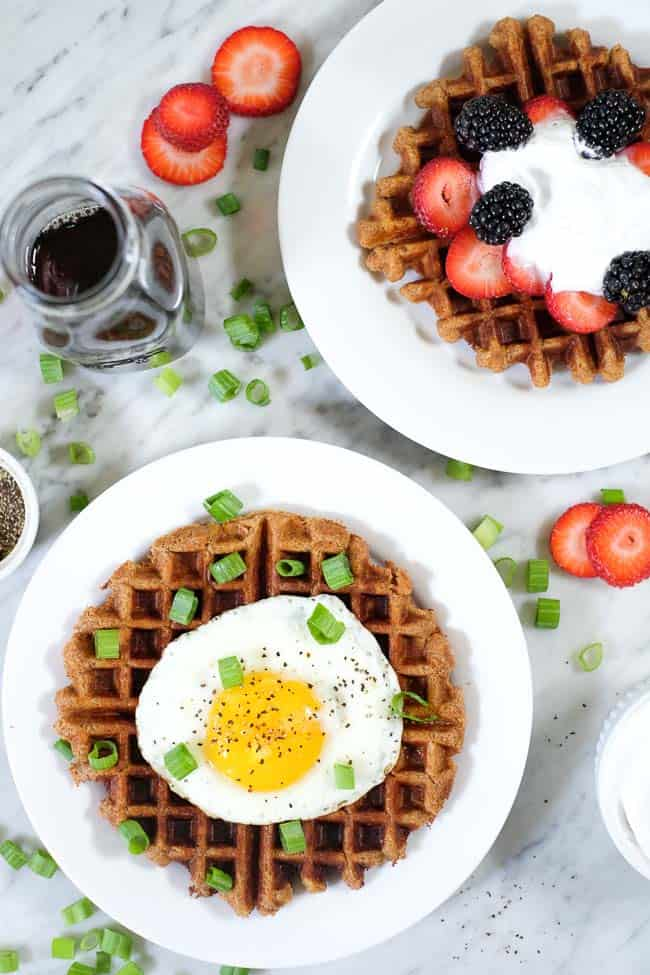 Sweet and savory Paleo waffles. One topped with berries and coconut whipped cream and the other with a fried egg and green onion.