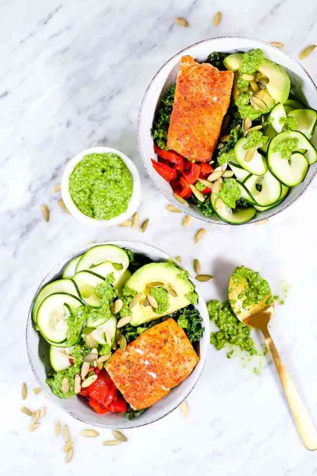 Salmon kale veggie bowl with pesto sauce and pumpkin seeds pulled out shot