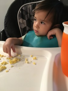 image on real simple mama of toddler in a high chair wearing a bib eating some scrambled eggs and blueberries