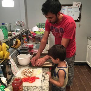 image of preschooler and daddy making their own pizza in the kitchen - real simple mama