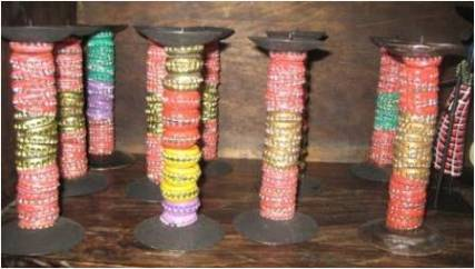 Bottle tops have also been used for many crafts such as these decorative candle sticks on sale in a craft shop.