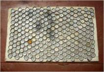 Bottle tops are abundant outside bars and restaurants. A very effective doormat or boot scraper can be made by nailing bottle tops onto a board.