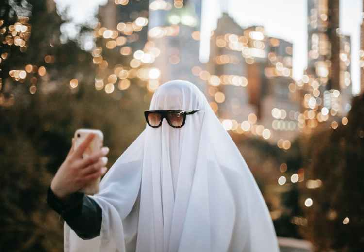 unrecognizable person in ghost costume taking selfie