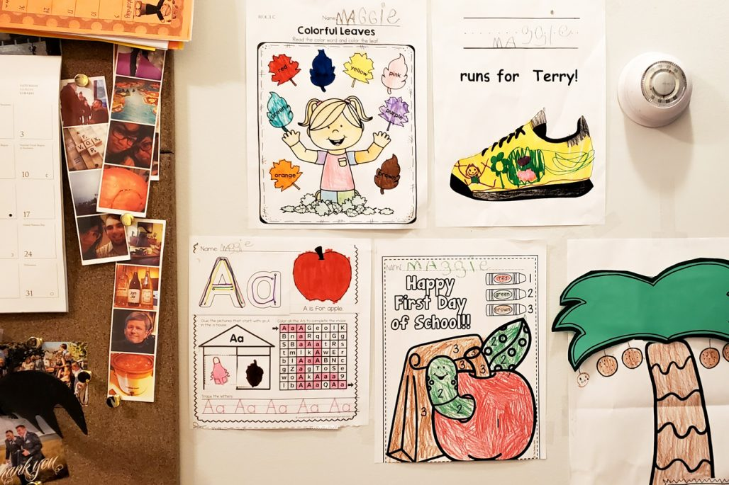 Image of a child's kindergarten assignments on the wall.