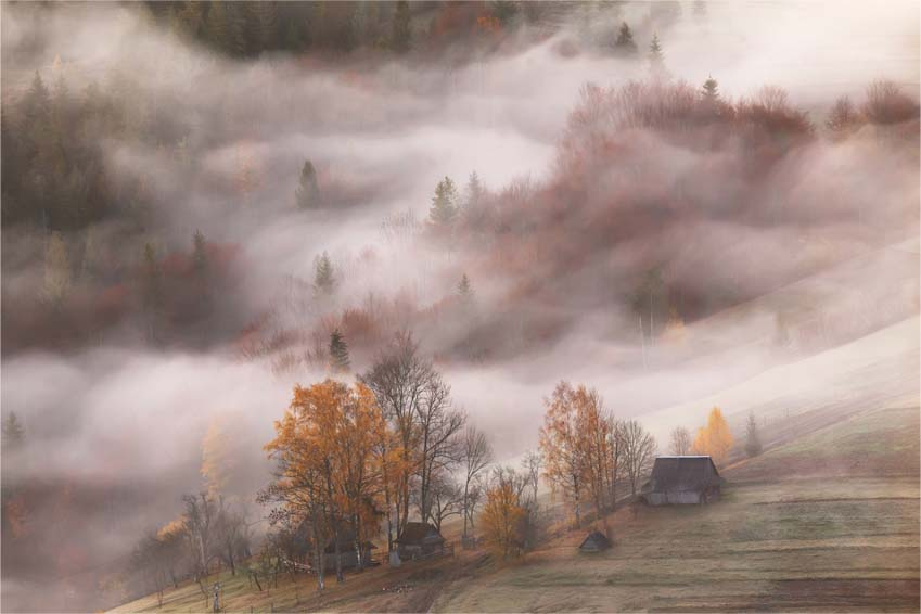 Mountain village in clouds of fog and smoke in the autumn morning