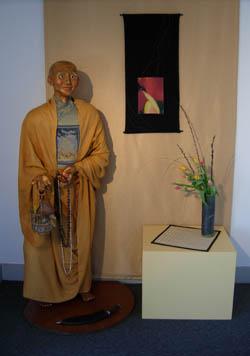 avie, life size, sculpture, ceramic, buddhist, monk, figure, cage, smiling, tibet, tibetan, saffron, robes, figurative, art, artwork, rebekah, younger