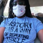 Black nonbinary woman sits in a car after voting. She's wearing a blue shirt with black letters that spell out 'History has a way of repeating itself itself itself, and a white facemask with a 'I Voted In Dallas County sticker.'